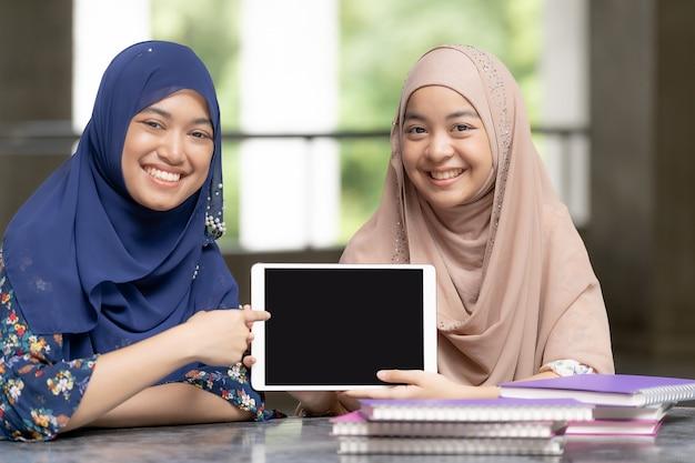 Moslemische studenten des jugendlichen mit tablette