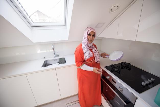 Moslemische traditionelle kleidungsfrau in der weißen modernen küche