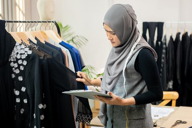 Moslemischer frauendesigner als startgeschäftseigentümer, der im schneidershop arbeitet