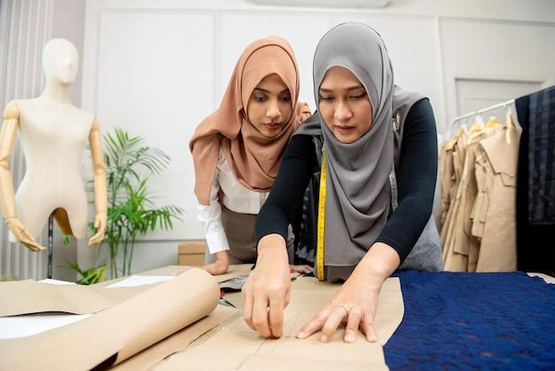 Moslemischer frauenmodedesigner, der papiermuster auf gewebe feststeckt