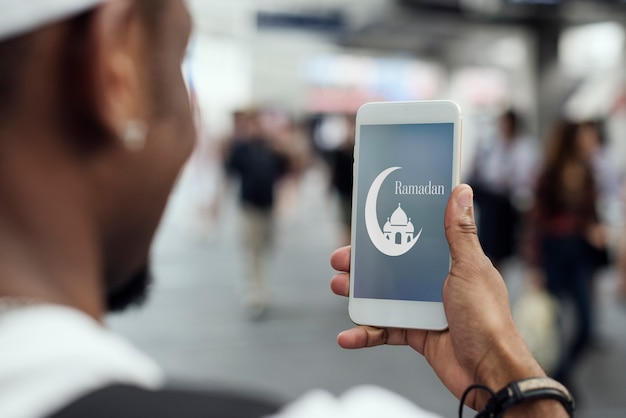 Moslemischer junge, der einen smartphone verwendet