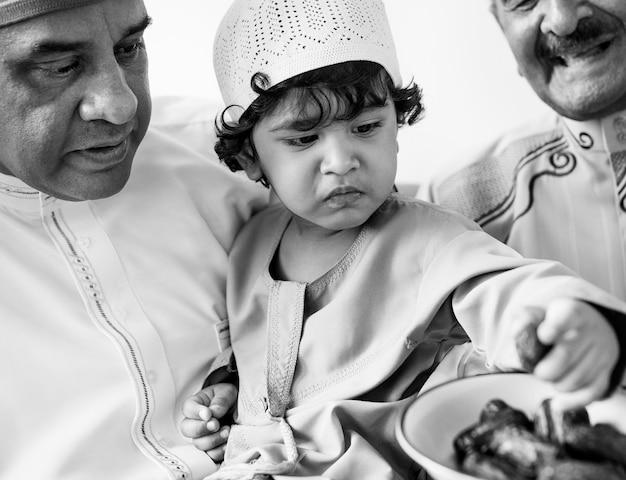 Moslemischer junge, der getrocknete daten isst