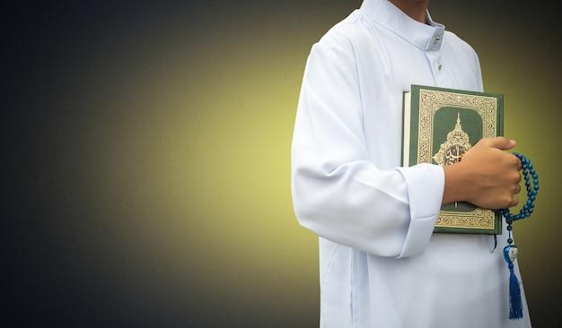 Moslemischer junge, der heiligen quran hält
