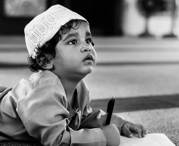 Moslemischer junge, der in einer moschee lernt