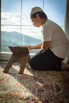 Moslemischer junge, der koran liest und für gott betet