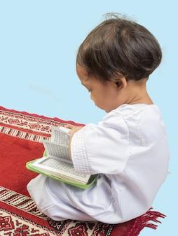 Moslemischer junge in einem kleid den koran lesend