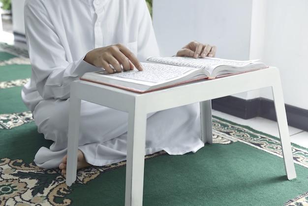 Moslemischer mann, der auf teppich sitzt und den koran liest