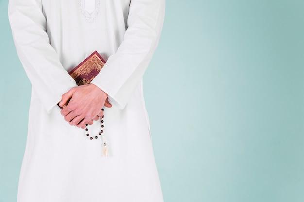 Moslemischer mann, der koran hält