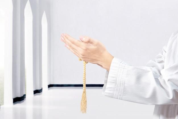 Moslemischer mann, der mit gebetsperlen auf seinen händen betet