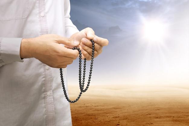 Moslemischer mann, der mit gebetsperlen auf seinen händen in der wüste betet