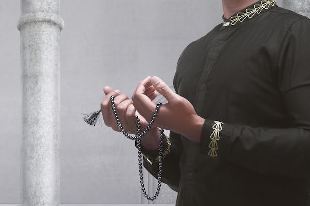 Moslemischer mann, der mit gebetsperlen betet