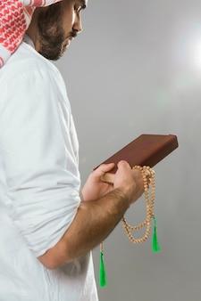 Moslemischer mann, der quran hält und perle betet