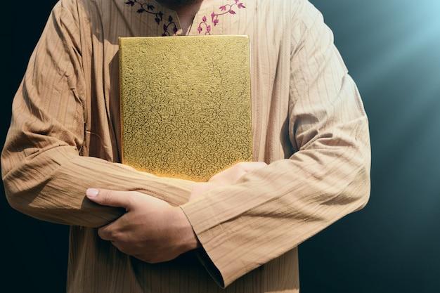 Moslemischer mann, der quran hält