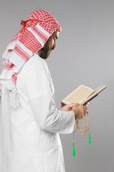 Moslemischer mann, der vom quran liest und betende perlen hält