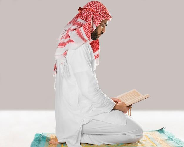Moslemischer mann, der vom quran sitzt und liest