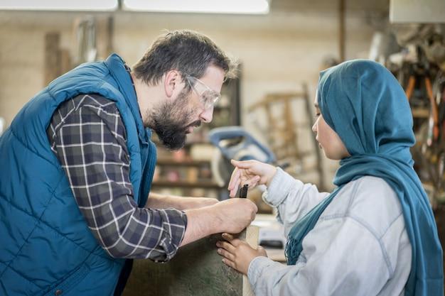 Moslemischer mann und frau in der werkstatt, die zusammenarbeitet
