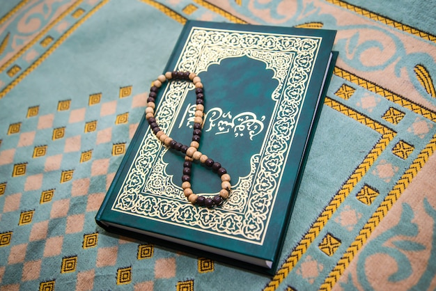 Moslemischer rosenkranz und gebetbuch auf dem teppich