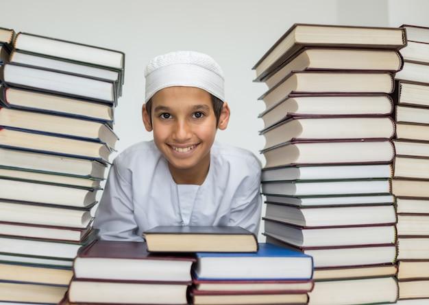 Moslemisches arabisches kind in der bibliothek mit büchern
