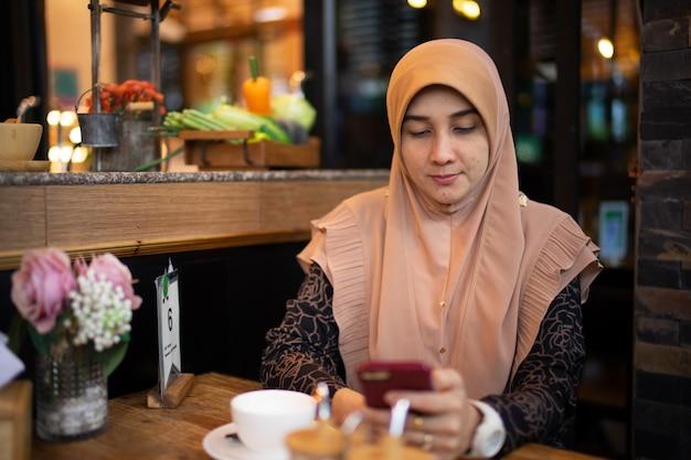 Moslemisches frauenkleid mit dem hijab und moslemischem stoff, handy im restaurant spielend.