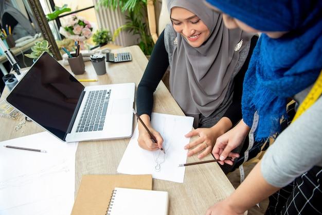 Moslemisches frauenmodedesignerteam, das kleidsskizze bespricht