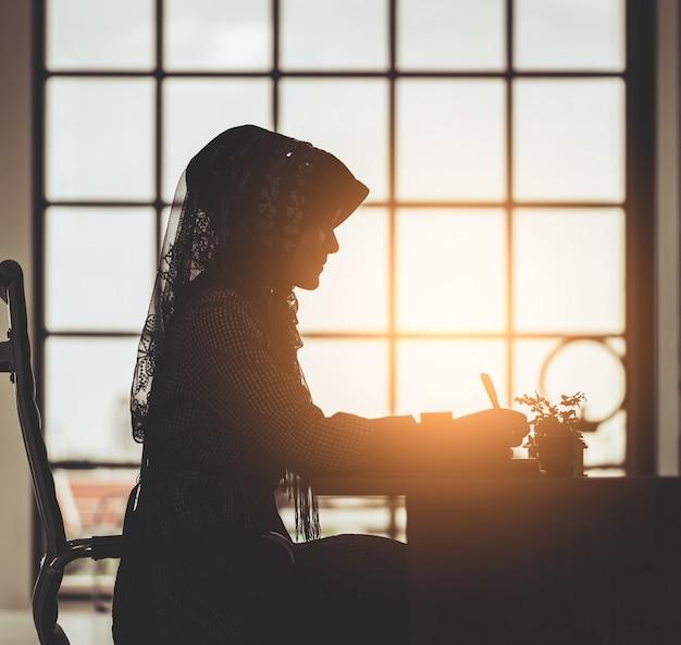 Moslemisches geschäftsleute konzept - schattenbild der islamfrau arbeitend an bürotischfenster-morgenaufflackern