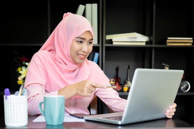 Moslemisches hemdrosa der asiatin. geschäftsfrauen übergeben mit dem papierschreiben am diagramm und verwenden den computer-notizbuchlaptop und -smartphone und fällen glückliches marketing-geschäft für erfolgs-konzept.