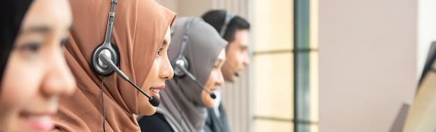 Moslemisches kundendienstbetreiberteam, das im call-center-büro arbeitet