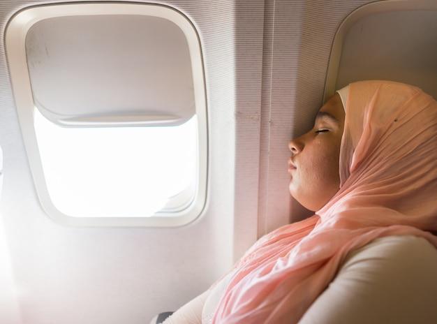 Moslemisches mädchen, das im flugzeug schläft