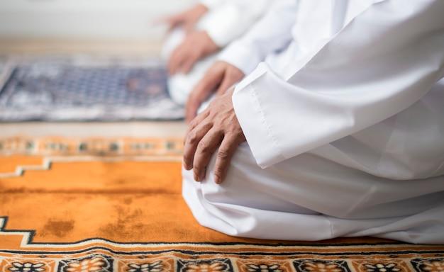 Moslems beten in tashahhud-haltung
