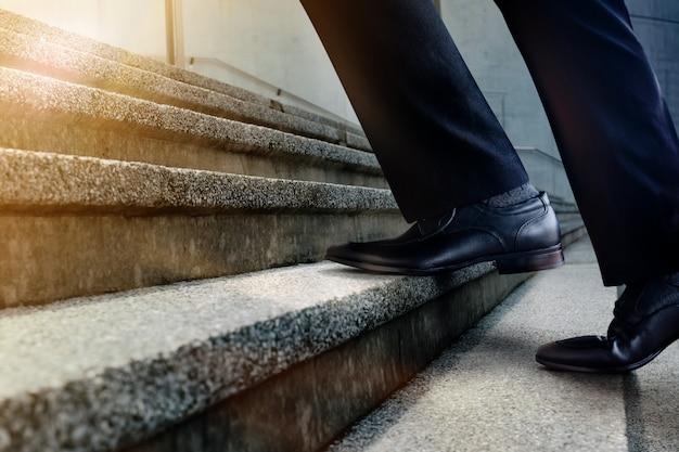 Motivation und herausforderndes karrierekonzept. schritte vorwärts zum erfolg. niedriger abschnitt des geschäftsmannes gehend oben auf treppenhaus. mann im schwarzen formellen kleid