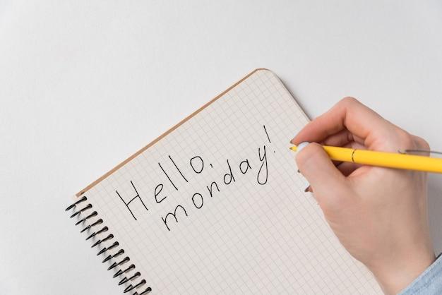 Motivationsschreiben im notizblock hallo montag. guten start in die woche. weibliche hand schreibt.