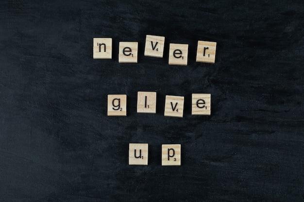 Motivierende und inspirierende zitate mit geschnitzten holzbuchstaben auf der tafel.