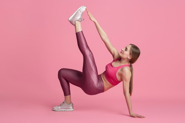 Motiviert. schöne junge sportlerin üben, einfarbiges rosa porträt. kaukasisches modelltraining mit sportlicher passform. bodybuilding, gesunder lebensstil, schönheits- und aktionskonzept.