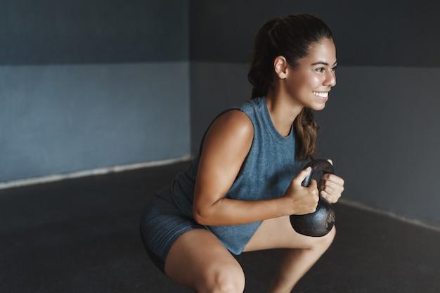 Motivierte gut aussehende sportliche junge frau, die kniebeugen mit kettlebell tut
