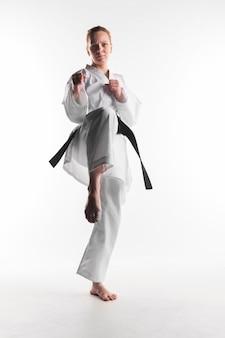 Motivierte karatefrau, die vorderansicht tritt