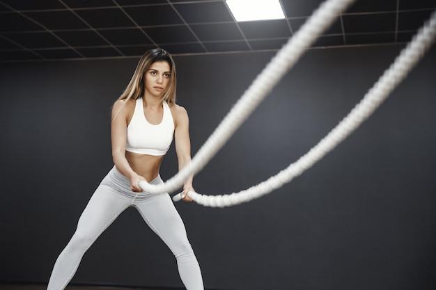 Motivierte starke und fit aussehende sportlerin, sportlerin in weißer aktivkleidung führt trainingsübungen mit kampfseilen im fitnessstudio durch
