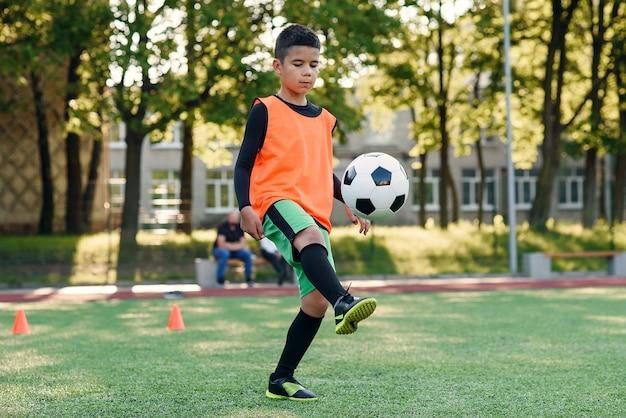 Motivierter jugendlicher fußballspieler stopft fußball mit stiefeln auf füße