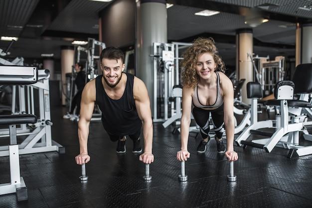 Motivierter junger blonder frauen- und manntrainer mitten im training, stehend in planke mit hanteln.