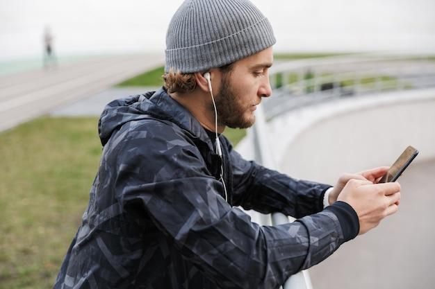 Motivierter junger fitter sportler, der musik mit kopfhörern hört, während er im stadion steht, handy benutzt und sich an die schiene lehnt