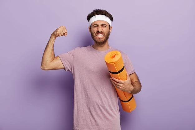 Motivierter kraftvoller mann steht mit fitnessmatte, genießt yoga als sport und hobby, hebt den arm und zeigt muskeln, beißt zähne zusammen, trägt stirnband, violettes t-shirt. balancieren sie ihr leben, führen sie einen gesunden lebensstil