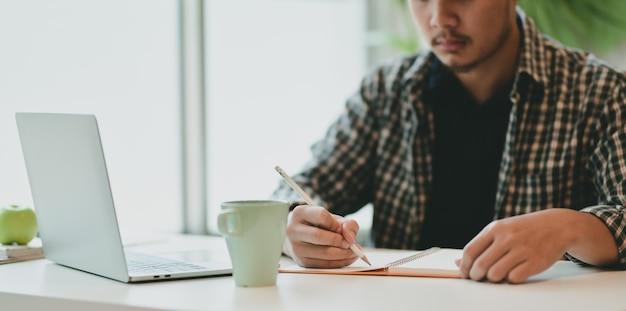Motivierter männlicher freier mitarbeiter, der seine idee auf notizbuch schreibt