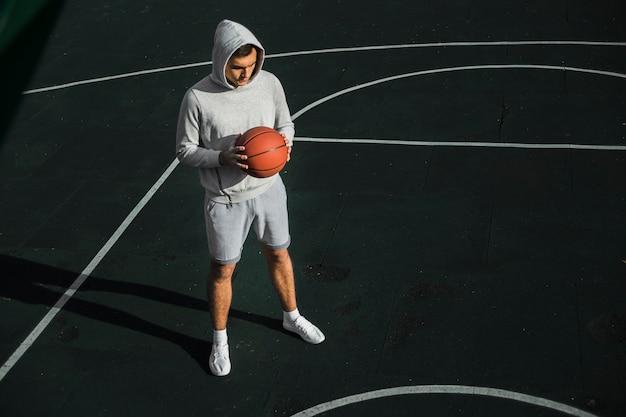Motivierter spieler, der basketball hält