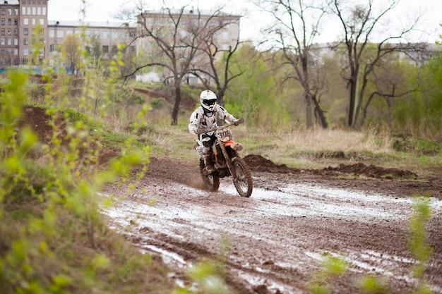 Motocross-fahrer, der sich auf einer schlammpiste bewegt