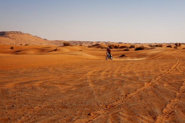 Motocross-fahrer fährt motorrad in der wüste