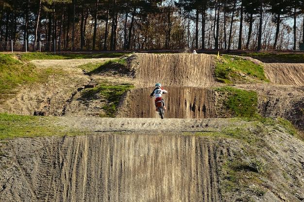 Motocross-fahrer in aktion beschleunigt das motorrad auf der rennstrecke
