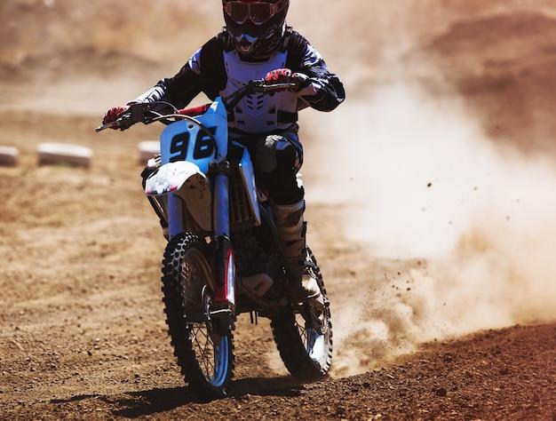 Motocross-rennfahrer beschleunigt auf staubspur getöntes foto