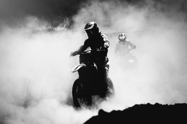 Motocross-rennfahrer beschleunigt auf staubspur schwarzweißfoto mit hohem kontrast