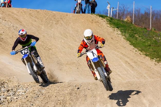 Motocross-wettbewerbe zwei fahrer fahren im staub die strecke entlang