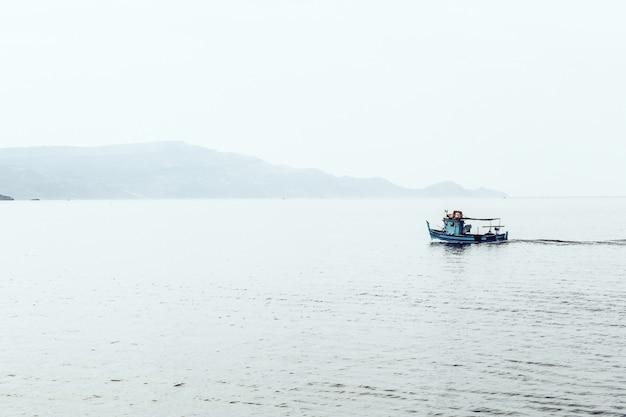 Motorboot auf dem meer umgeben von bergen im nebel