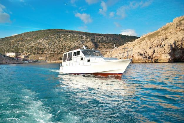 Motorboot, das das meer nahe der küste kreuzt. seelandschaft